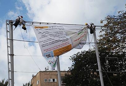 """פעילי גרינפיס תולים את הדו""""ח הענק (צילום: מוטי קמחי)"""