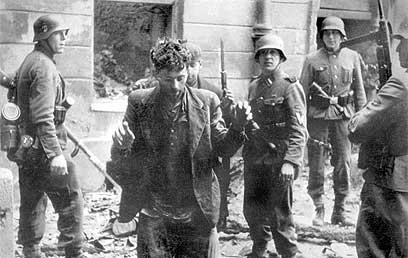 חיילים נאצים עוצרים יהודי בגטו ורשה ב-1943 (צילום: איי פי)