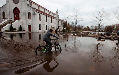 רוכב אופניים בסטטן איילנד המוצפת. אחד מאמצעי התחבורה היחידים שלא נפגע בעקבות הסופה (צילום: רויטרס)
