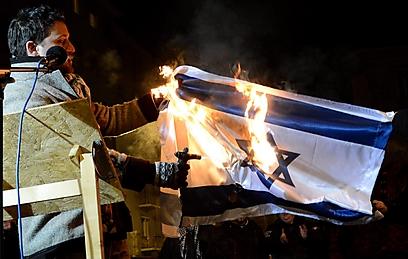 חבר הפרלמנט מצית את הדגל (צילום: EPA)