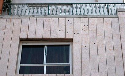 סימני הקליעים על קיר הבניין בלוד (צילום: אבי מועלם)
