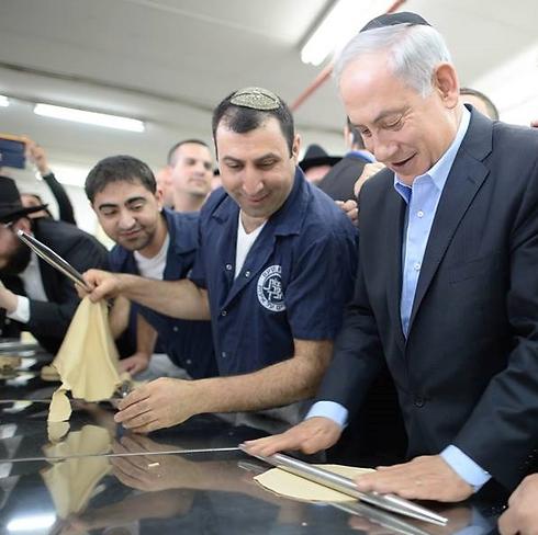 Netanyahu flattening a matzah (Photo: Kobi Gideon, GPO)