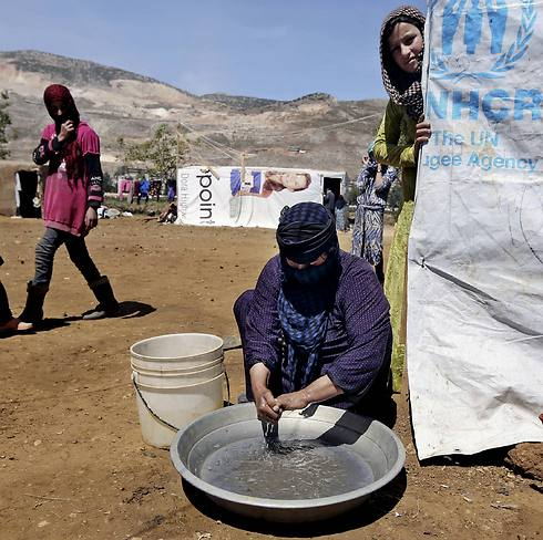 Halbiya, 50, who fled her home from Deir al-Zour, washes her hands after working on a field, at a Syrian refugee camp in Lebanon (Photo: AP) (Photo: AP)