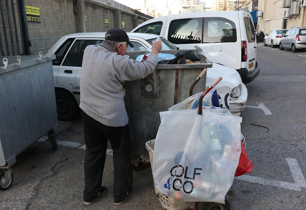 An elderly Israeli man searches in the trash   (Photo: Shaul Golan)