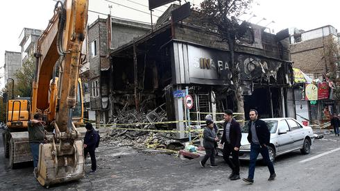 Iranians walk past a bank burned by protesters in Tehran  (Photo: Reuters)