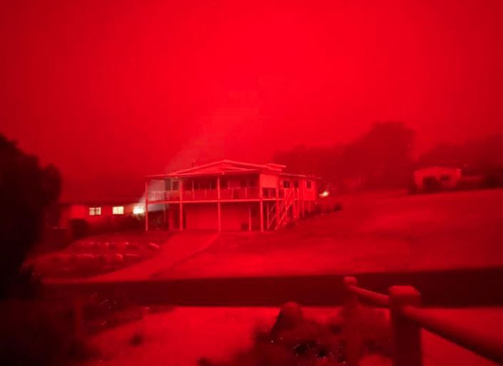 A red haze hangs over Mallacoota as devastating wildfires sweep the state of Victoria ()