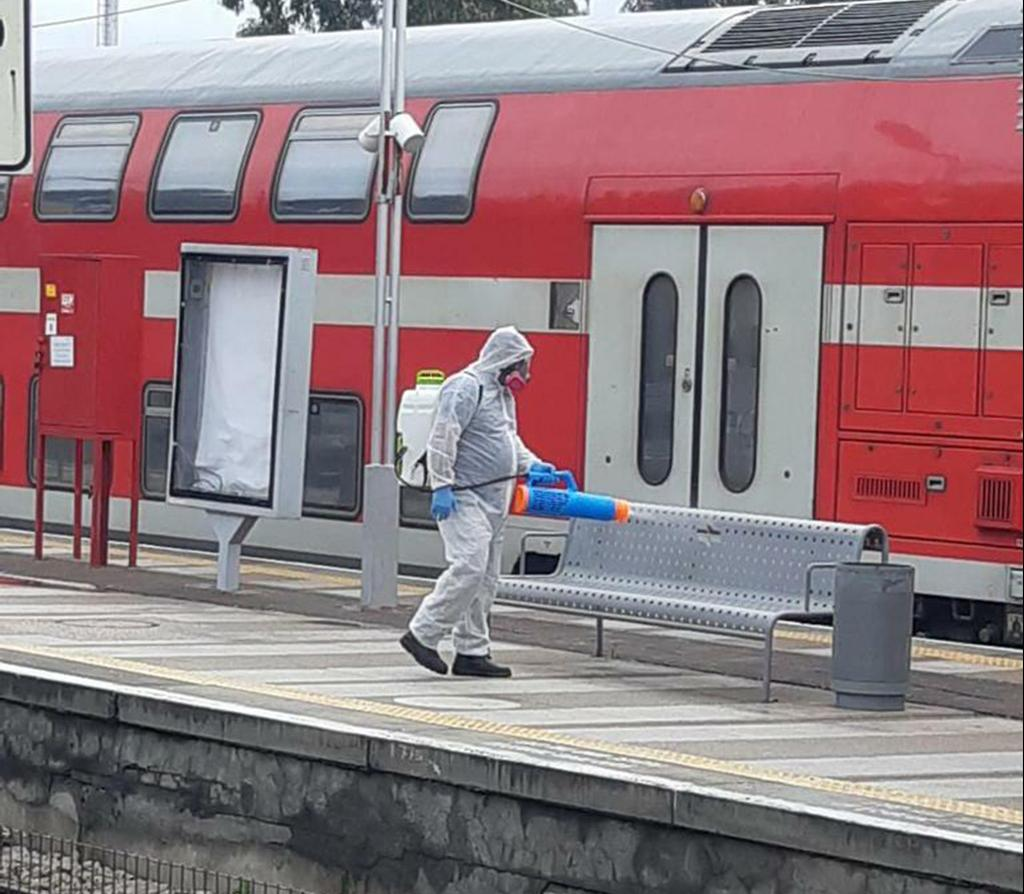 A worker disinfects a train platform  ()