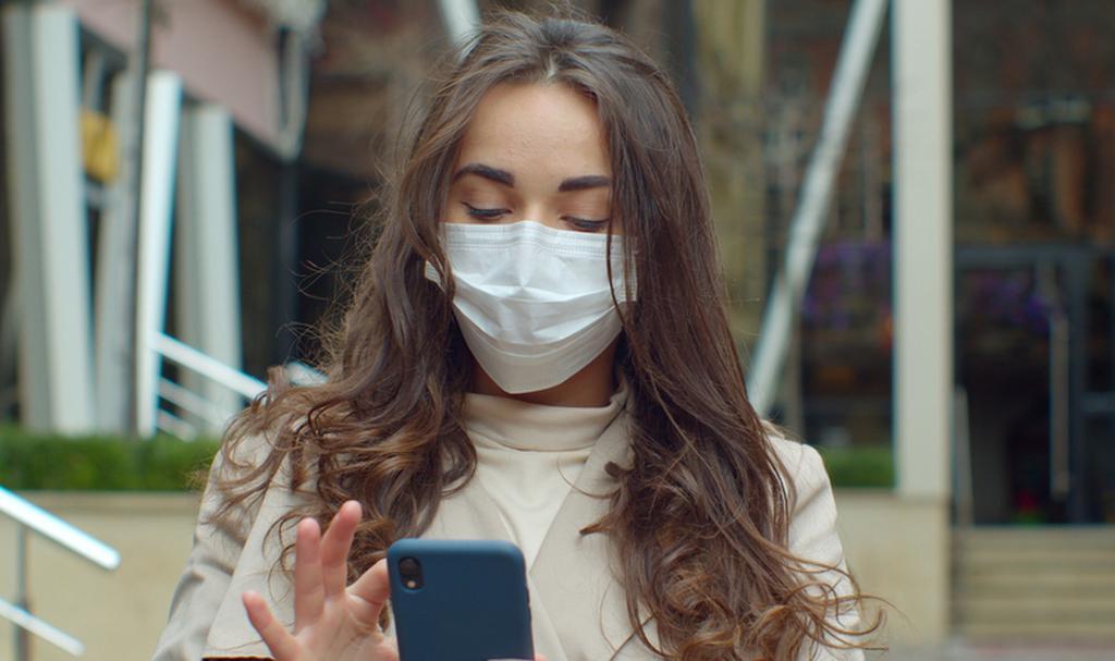 אישה עם מסכה וסמארטפון (צילום: shutterstock)