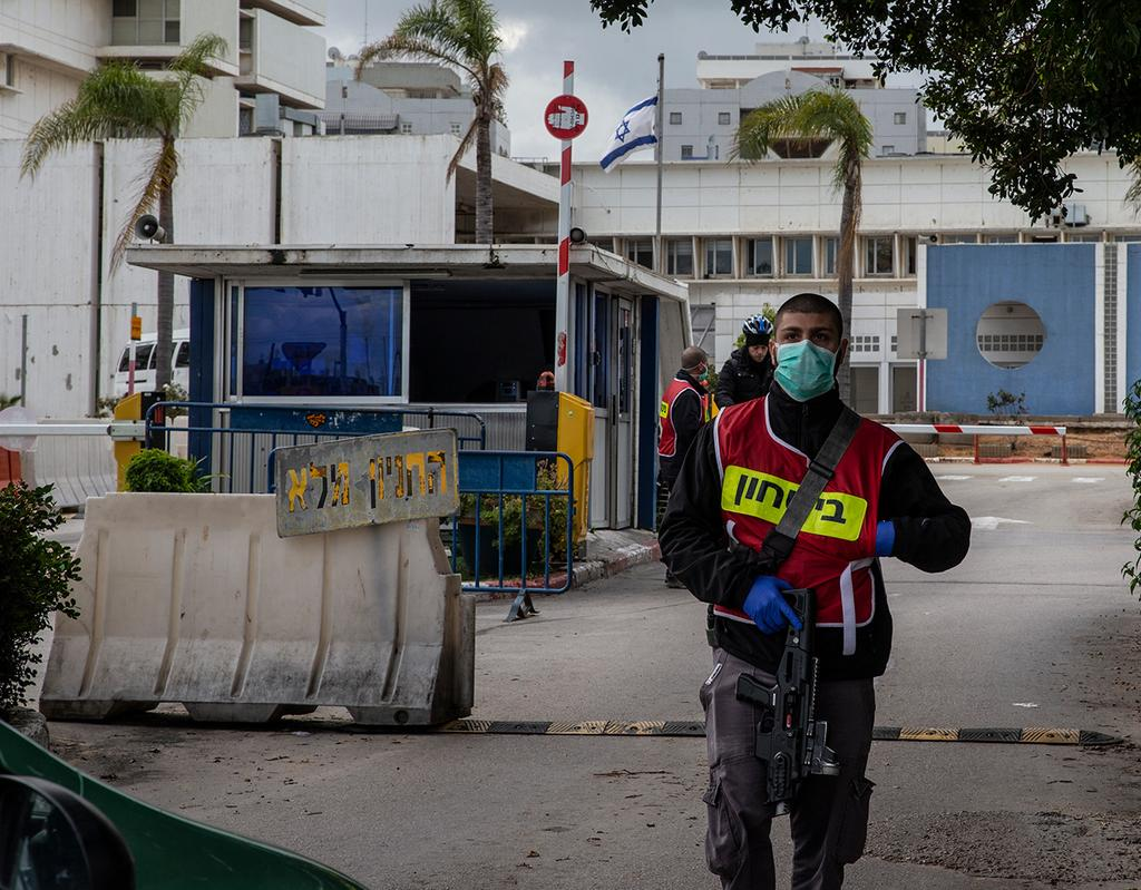 A guard wears a mask against coronavirus at the entrance to Wolfson Hospital in Holon ()