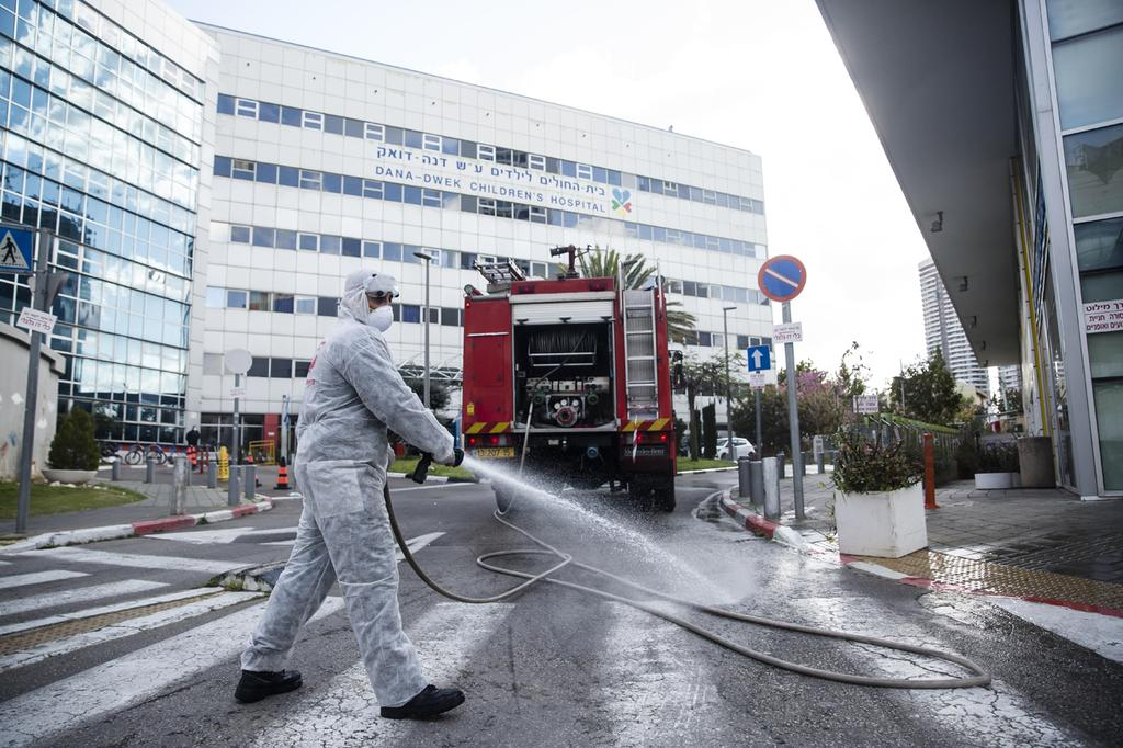 A worker disinfects the entrance to Ichilov Hospital in Tel Aviv  ()