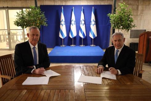 Blue & White Chairman Benny Gantz and Prime Minister Benjamin Netanyahu signing the coalition deal ()