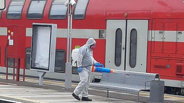 Sanitation worker disinfecting a train station  ()