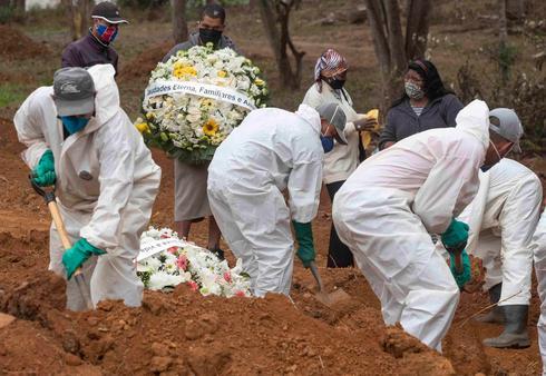 Undertakers in Brazil, wearing protective gear, bury coronavirus victims  ()