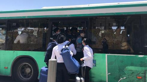 People line up to board a crowded bus  ()