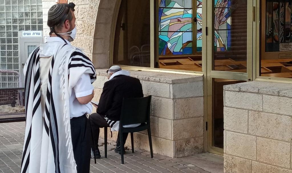 מתפלל במרחק נגיעה מבית הכנסת (צילום: שמחה הלר)