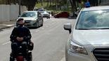 תיעוד: רכב משטרה חנה על המדרכה, נכה עם כיסא גלגלים ירד לכביש